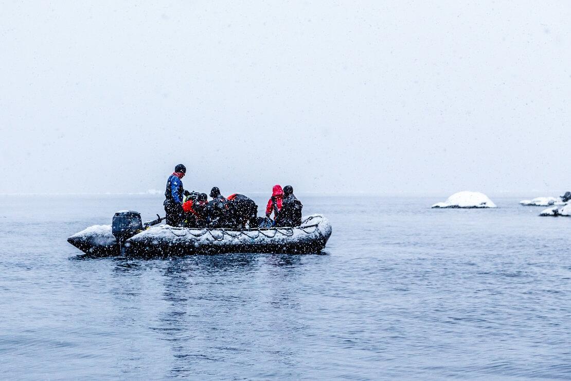 Menschen sitzen auf einem Schlauchboot in der Antarktis