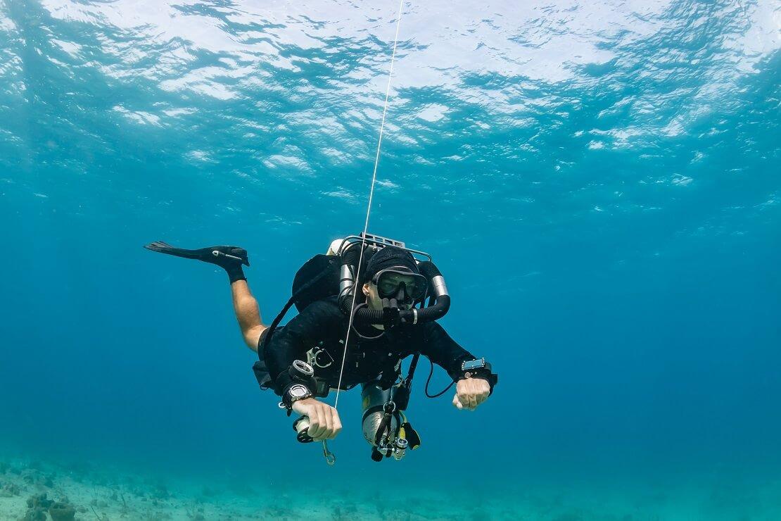 Taucher unter Wasser mit einer Schnur in der Hand