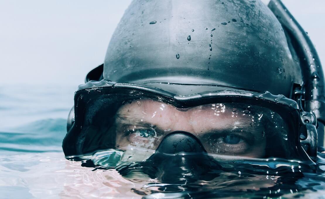 Taucher halb unter Wasser mit Tauchmaske
