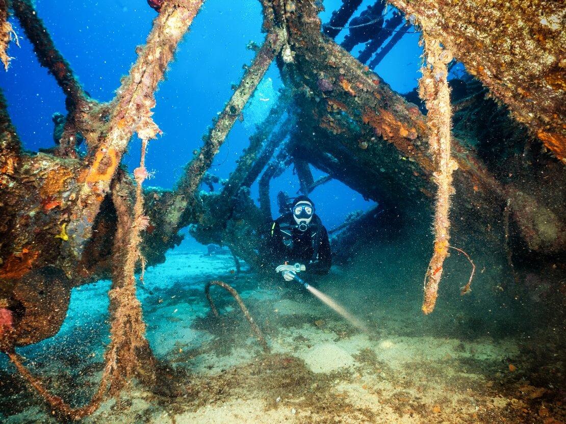 Taucher am Meeresgrund schwimmt durch ein Wrack bewachsen mit Korallen