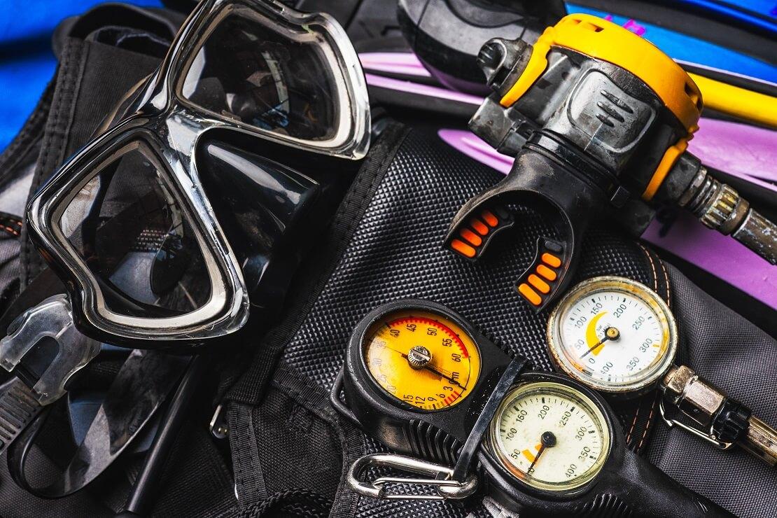 Taucherbrille und Atemregler liegen mit anderer Tauchausrüstung aufeinander