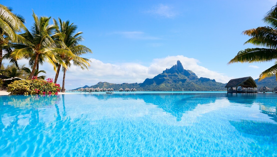 türkisblaues Wasser und Palmen im Hintergrund ist eine Insel