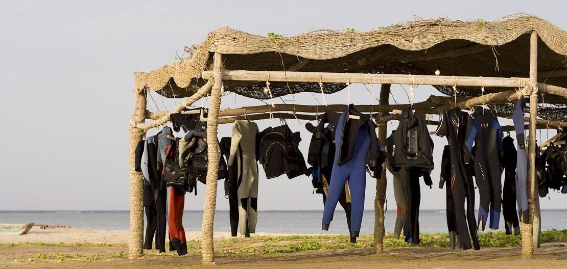 Tauchanzüge unter einem Sonnenschutz am Strand