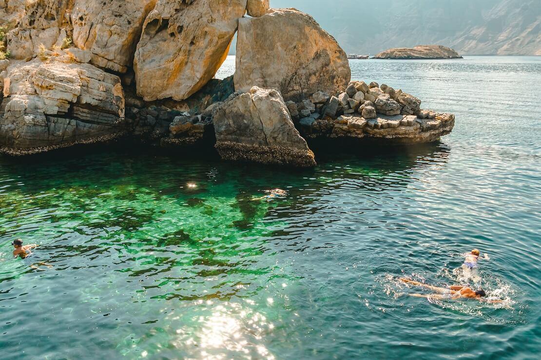 Taucher bei Oman im Hintergrund sind Felsen