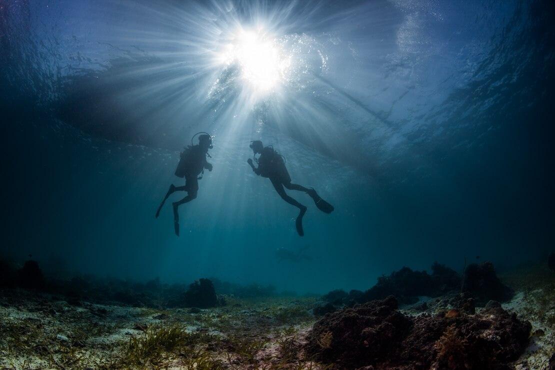Zwei Taucher am Meeresgrund mit Sonnenschein