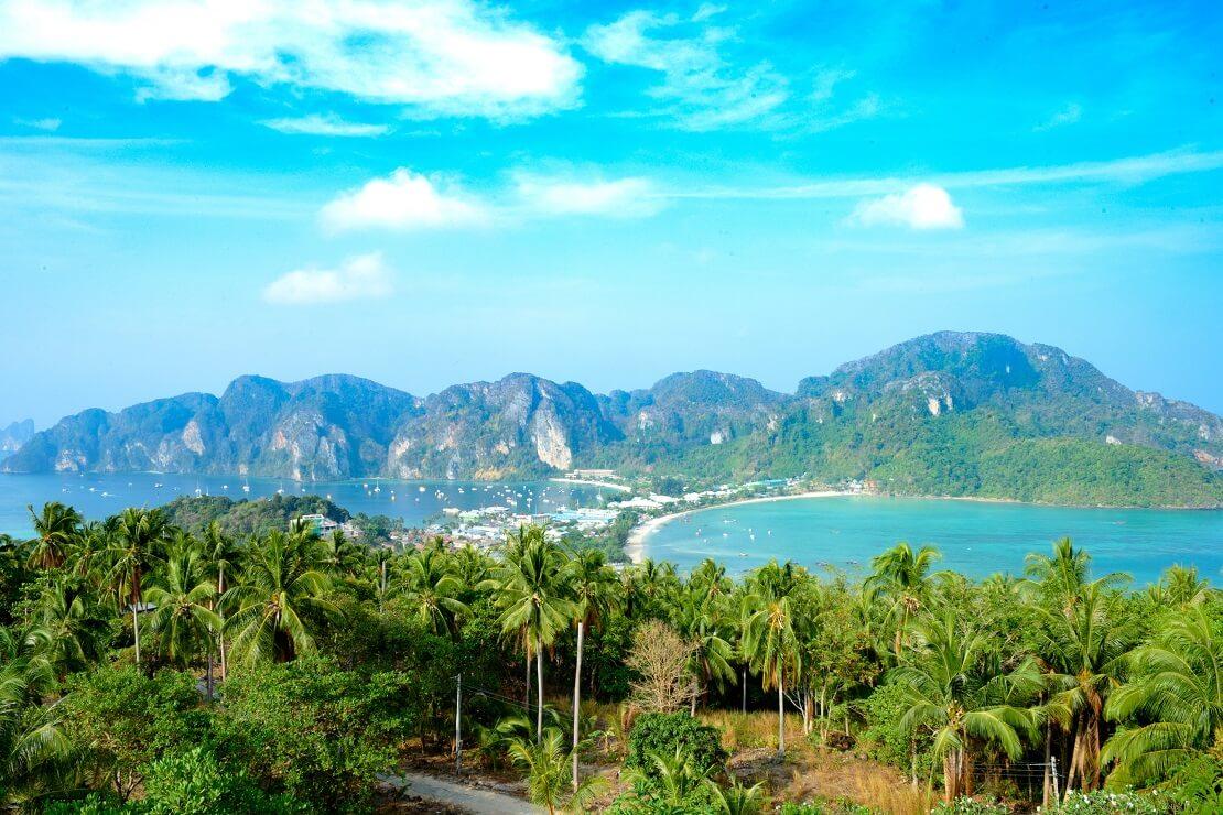 Anblick auf eine Insel mit Palmen und dem Meer im Hintergrund sind hohe Berge