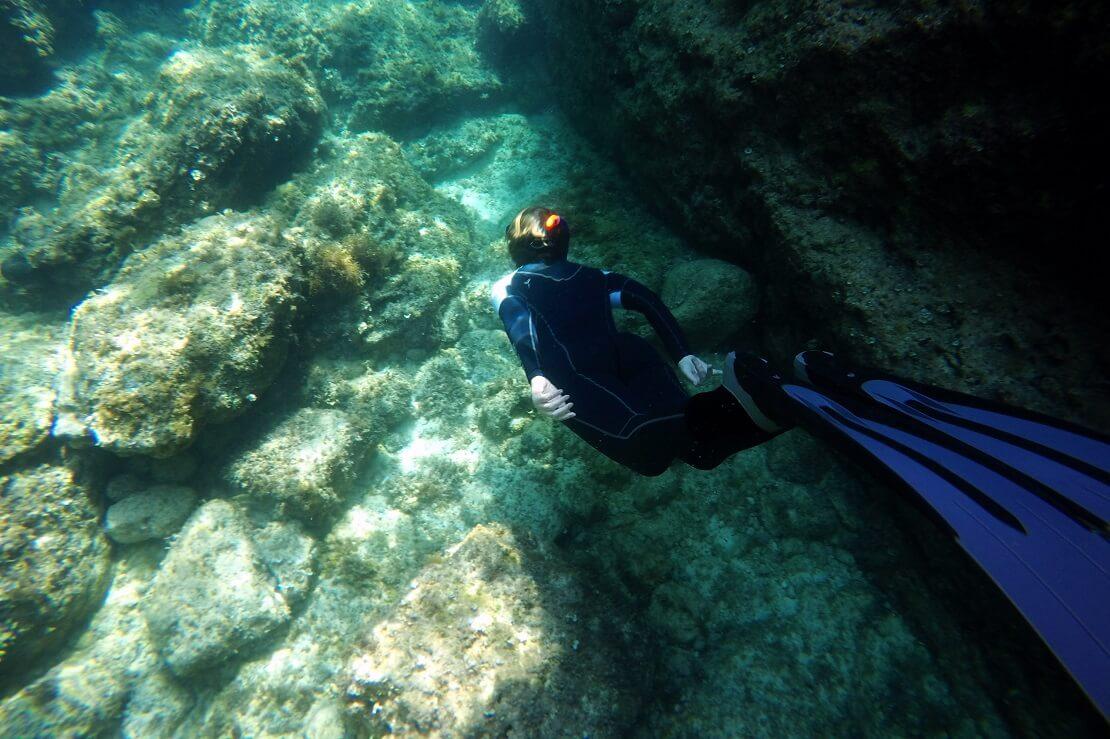 Apnoetaucher am Meeresgrund mit Felsen