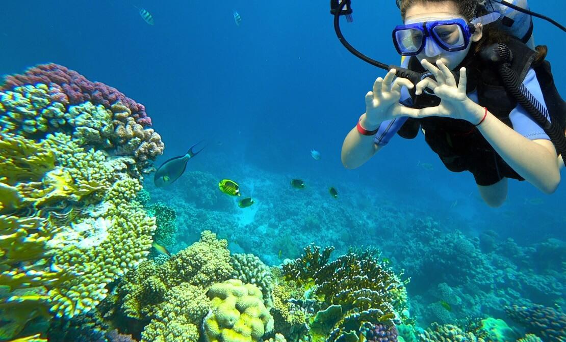 Kind an einem Korallenriff mit Tauchausrüstung