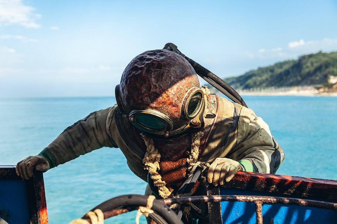 Taucher mit einem alten Tauchanzug steigt aus dem Wasser