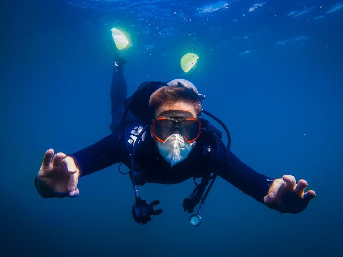 Taucher mit einer Mund-Nasen-Maske im Wasser