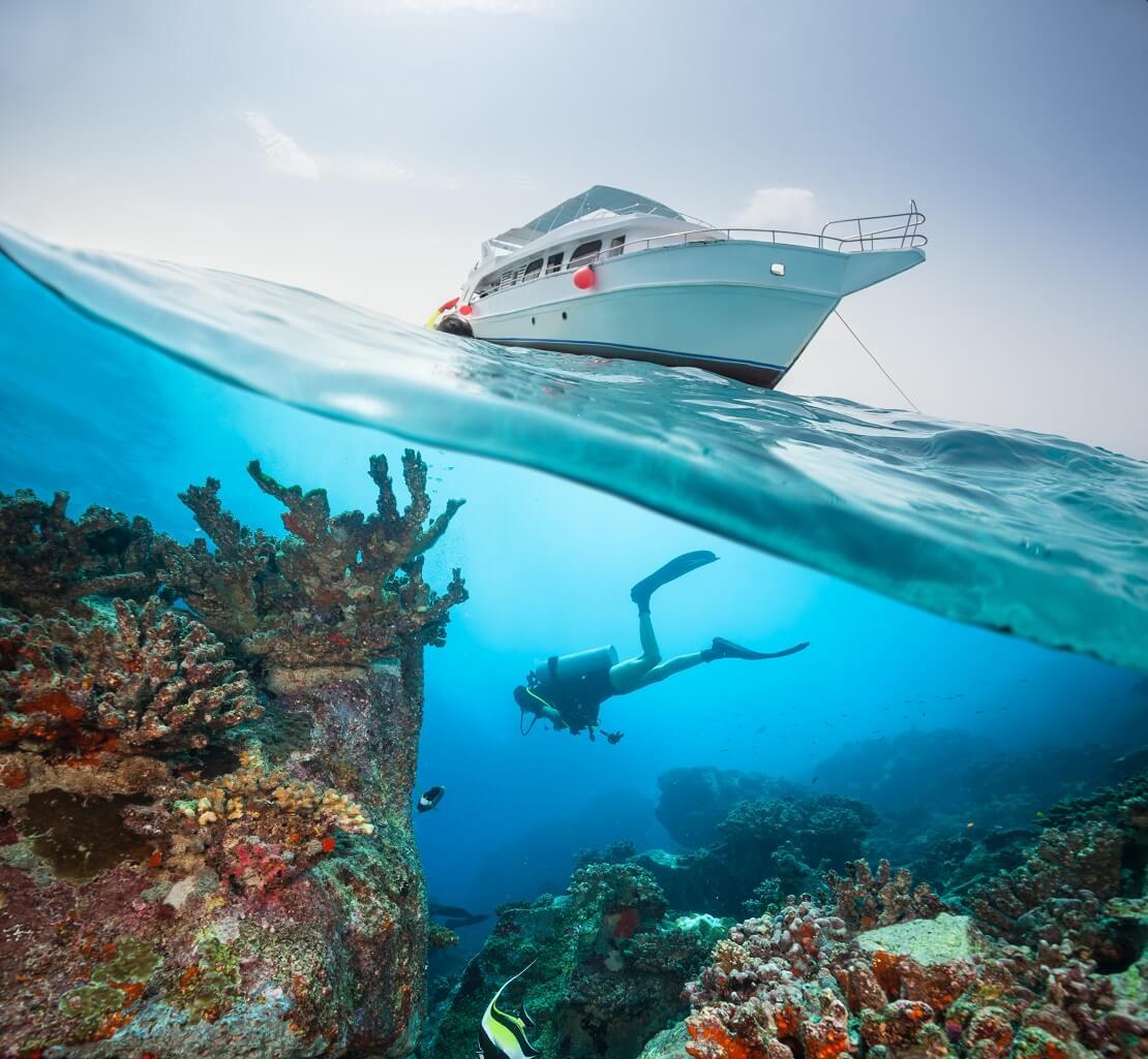 Taucher unter Wasser schwimmt unter einem Boot