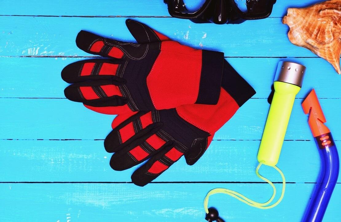 Rote Tauchhandschuhe legen auf einem Steg mit einer Taucherbrille, Schnorchel und einer Taschenlampe
