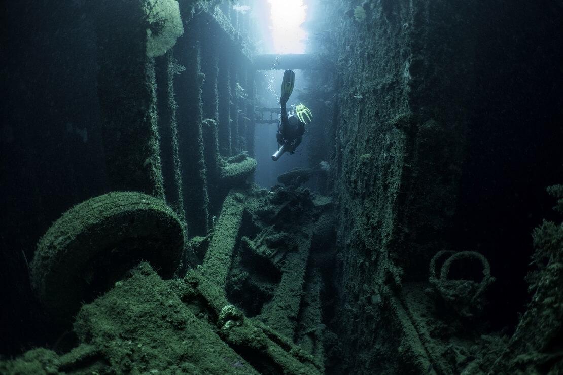 Taucher schwimmt durch das Wrack der SS President Collidge