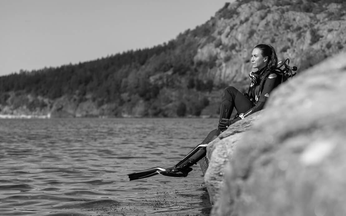 Taucherin sitzt auf einem Felsen mit dem neuen W7Anzug
