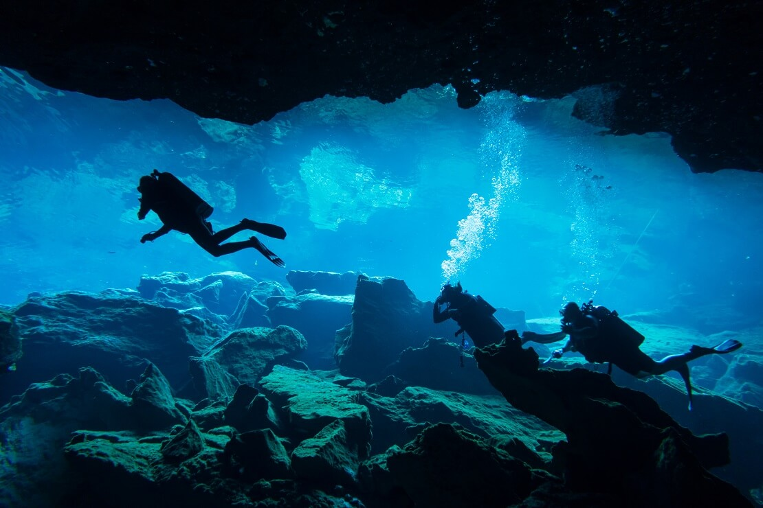 Drei Taucher in einer Unterwasserhöhle