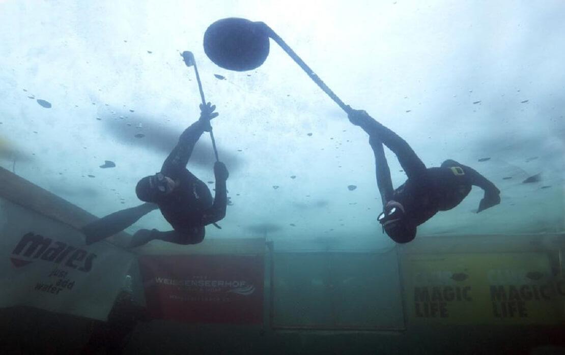 Zwei Spieler jagen den Puck im Unterwasser-Eishockey
