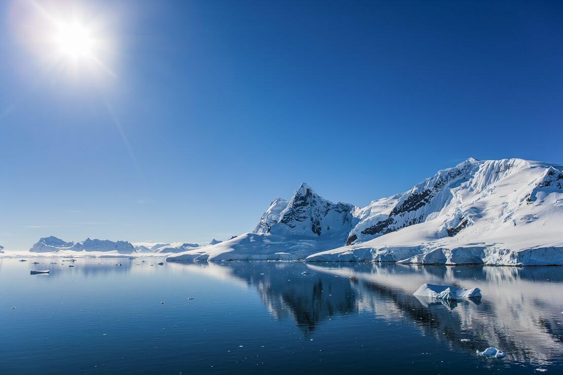 Die Antarktis mit tiefblauem Wasser und weißen Bergen
