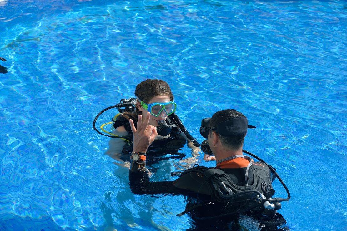 Tauchlehrer mit Schülerin im Schwimmbad