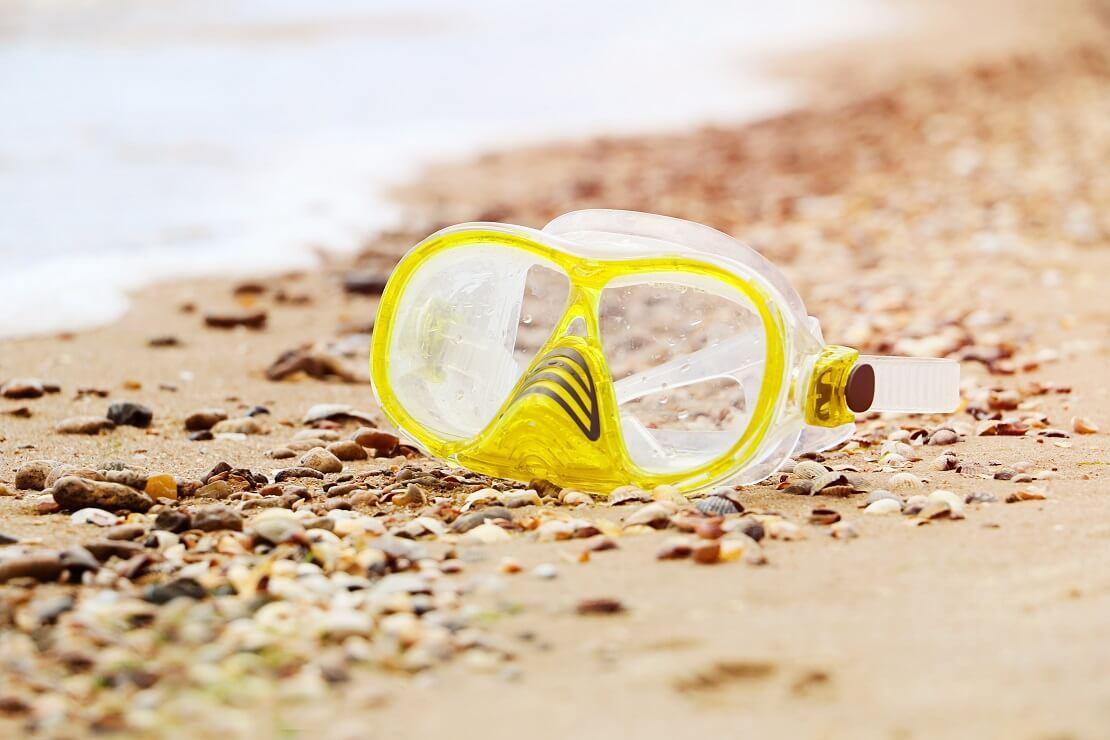 Gelbe Tauchmaske auf sandigem Boden