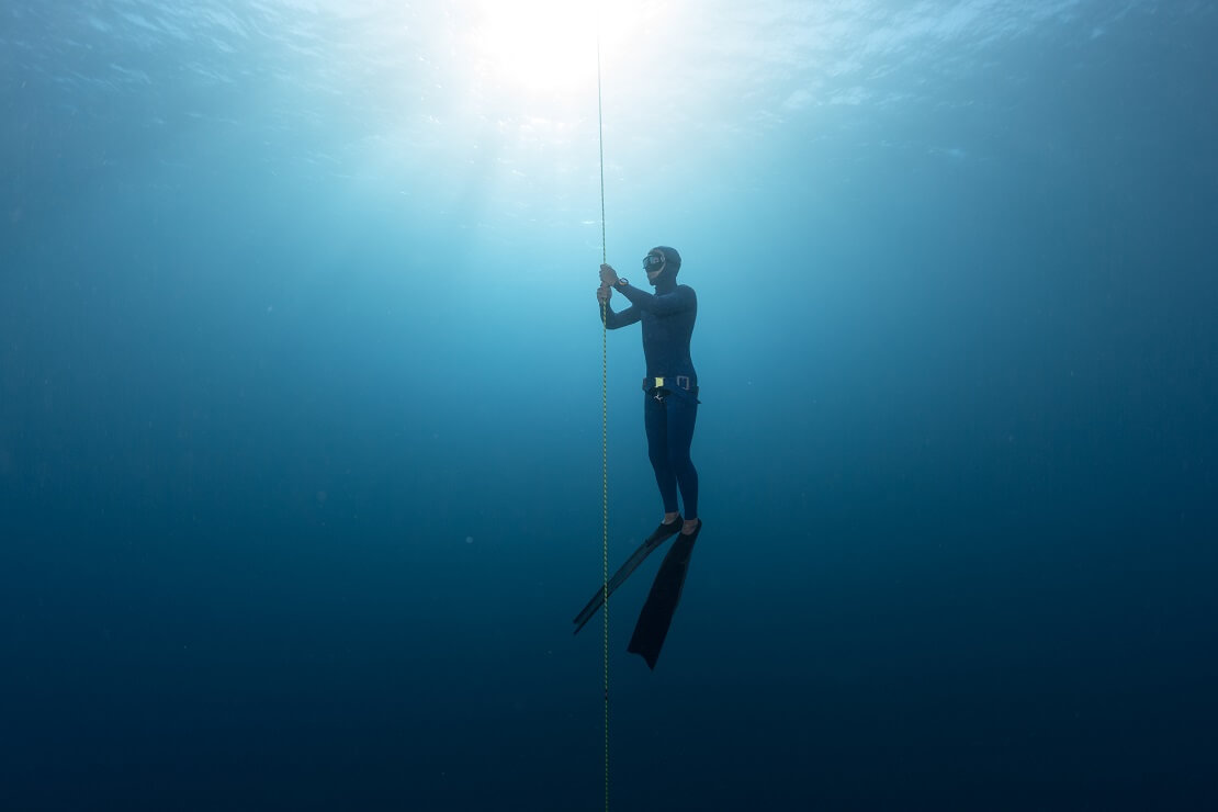 Apnoetaucher in tiefblauem Wasser