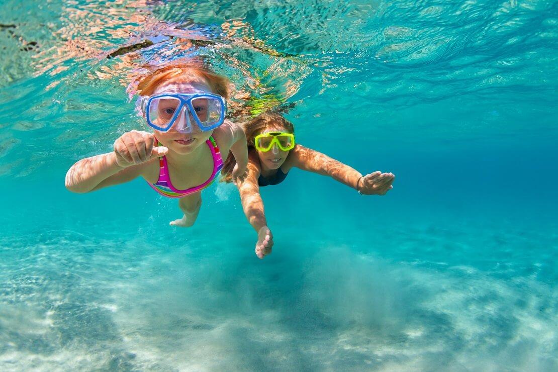 Zwei Kinder mit Tauchmasken unter Wasser